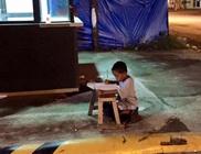 Az étterem kiszűrődő fényénél írja leckéjét a hajléktalan kisfiú